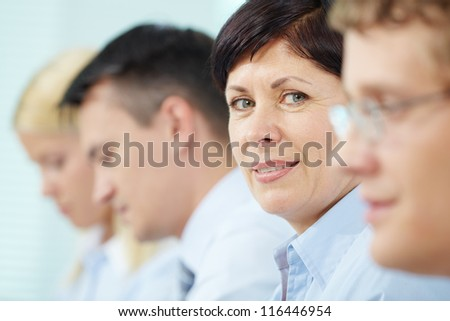 Mature businesswoman looking at camera between her partners - stock photo