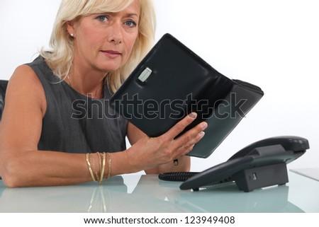 mature businesswoman looking at her agenda - stock photo