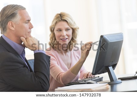 Mature businesswoman pointing at computer while sitting with male colleague in office - stock photo