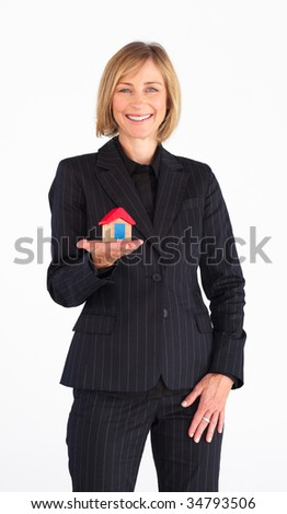 Mature businesswoman presenting a model of house - stock photo