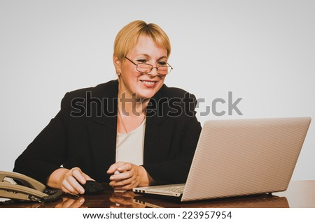 Mature businesswoman smiling while looking at screen of the laptop.