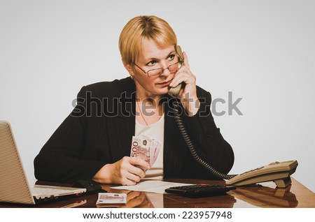 Mature businesswoman waiting for answer on the phone with money in hand. - stock photo