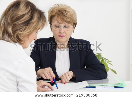 Mature businesswoman with client. - stock photo