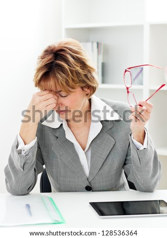 Mature businesswoman  with headache sitting at the table in the office. - stock photo