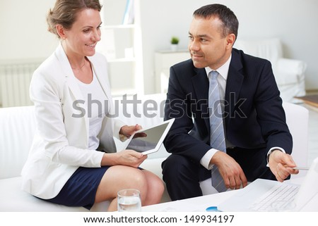Mature businesswoman with touchpad looking at laptop while discussing plans with her boss in office