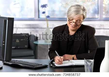 Mature businesswoman writing to personal organizer, looking down, smiling.