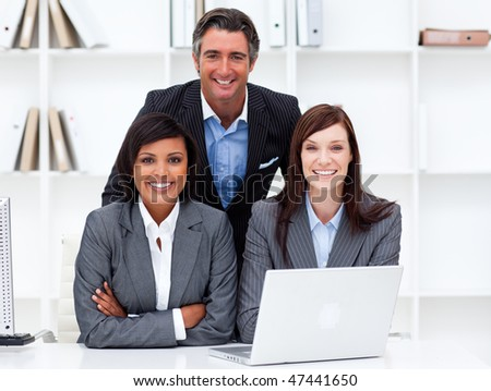 Mature businesswomen and their colleague working at a laptop in the office