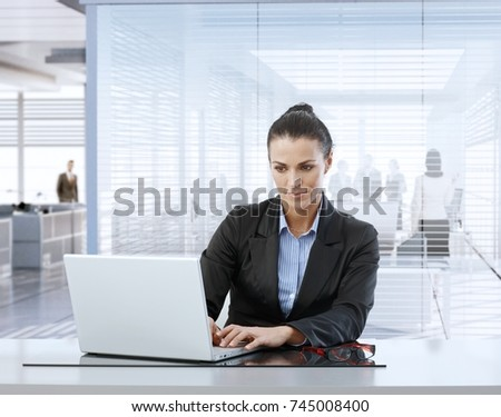 Mature caucasian businesswoman at work using laptop sitting at office desk.