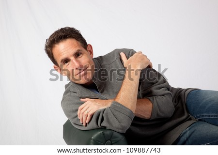 Mature Caucasian male reclining on a bench and smiling at the camera with a pleasing smile