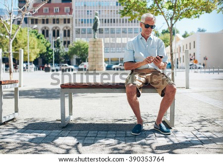 Mature caucasian man sitting on a bench in the city and using mobile phone. Senior tourist resting outside and texting by his cell phone. - stock photo