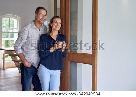 Mature Caucasian smiling couple standing at terrace door enjoying a weekend coffee break - stock photo