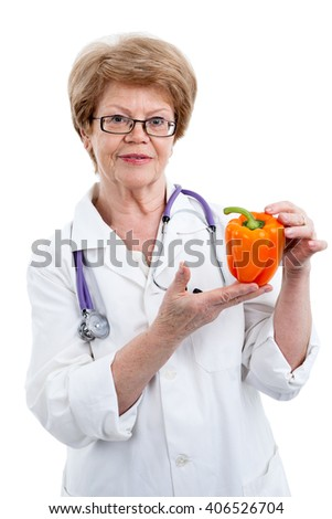 Mature Caucasian woman a doctor showing orange bell pepper in her hands, isolated on white background