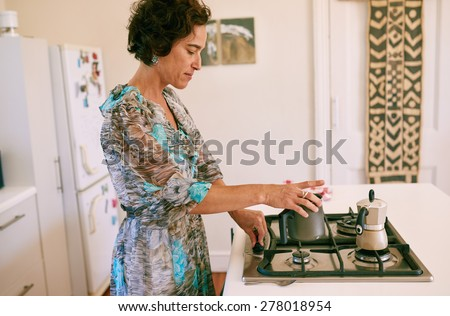 Mature caucasian woman preparing her morning cup of espresso coffee and warming up some milk on her gas stove in her white kitchen at home - stock photo