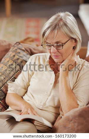 Mature Caucasian woman reading a book at home - stock photo