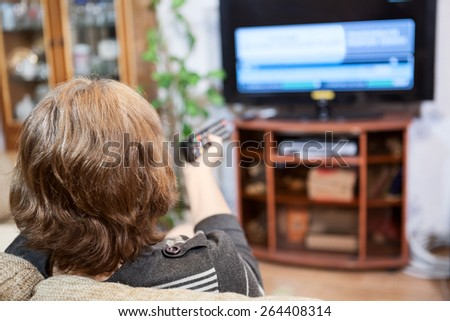 Mature Caucasian woman turning tv channels with remote control - stock photo