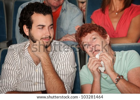 Mature Caucasian woman with tissue paper weeping in theater - stock photo