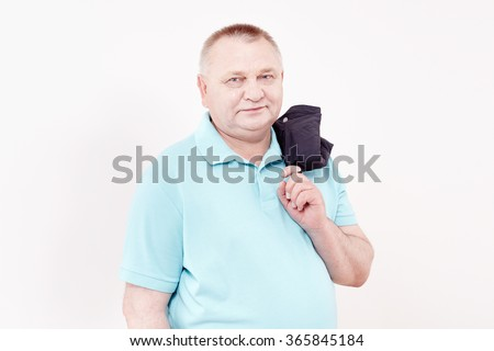 Mature cheerful man wearing blue shirt holding jacket over his shoulder and smiling against white wall - casual dress code concept - stock photo