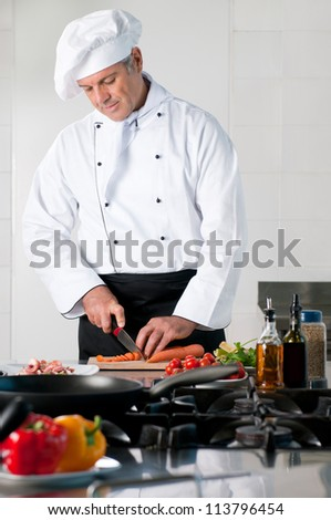 Mature chef cutting carrot at restaurant kitchen - stock photo