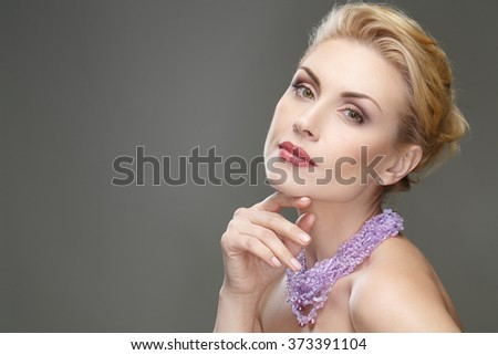 Mature chic. Portrait of a stunning blonde female wearing violet neckpiece looking at the camera touching her face - stock photo