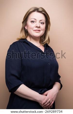 mature confident woman studio shot on brown background - stock photo