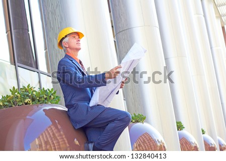Mature construction foreman looking up while holding blueprint. Horizontal shot.