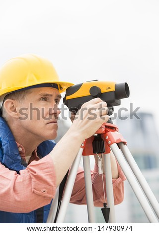 Mature construction worker measuring distances through theodolite at site