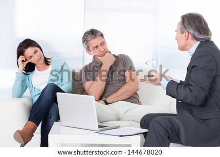 Mature Consultant Trying To Explain Worried Couple - stock photo