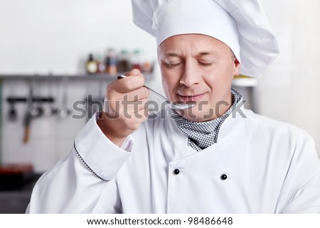 Mature cook prepares in the kitchen - stock photo