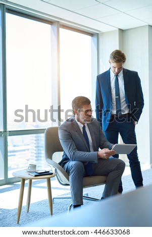 Mature corporate executive showing information on a digital tablet to a younger business employee - stock photo