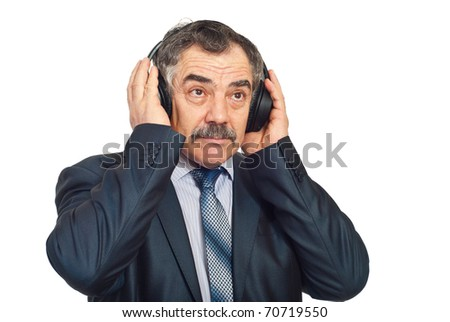 Mature corporate man listening music in headphones and looking up isolated on white background - stock photo