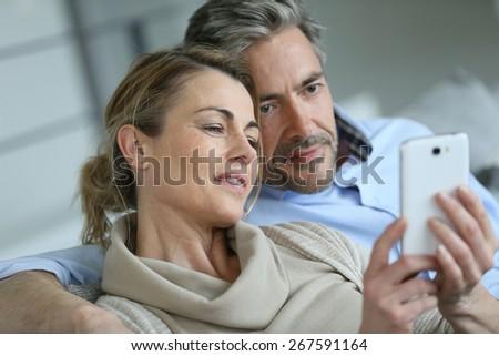 Mature coupel sittign in sofa and using smartphone - stock photo