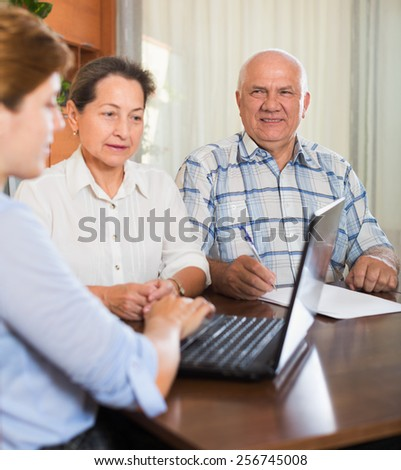 Mature couple answer questions of agent  with laptop in home - stock photo