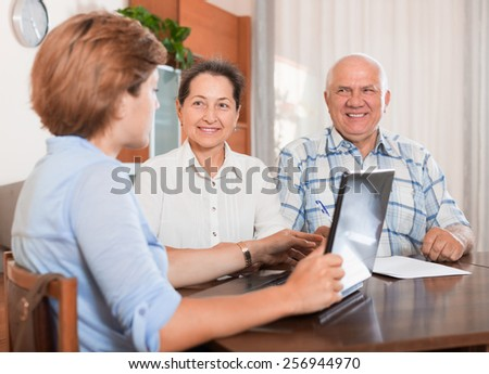 Mature couple answer questions of outreach worker with laptop in home - stock photo