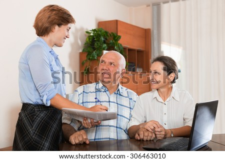 Mature couple answer questions of outreach worker with notebook in  office - stock photo