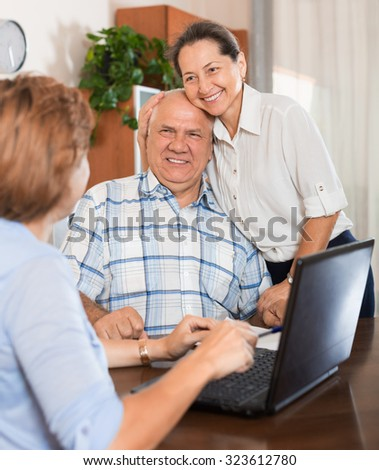 Mature couple answer questions of social worker with computer in  office - stock photo