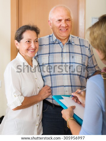 Mature couple answering the questions of young employee  in door at home