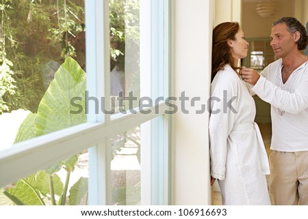 Mature couple being romantic by a garden's corridor, at home.