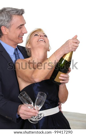 mature couple celebrating with champagne - stock photo