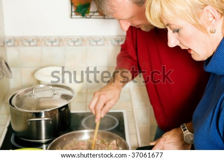 Mature couple cooking dinner together in their kitchen - stock photo