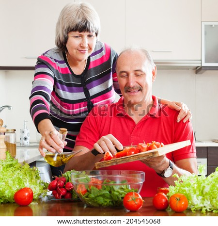 mature couple cooking  together in home kitchen