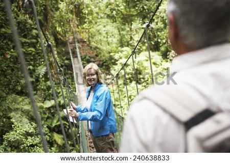 Mature Couple Crossing Rope Bridge in Wilderness Area