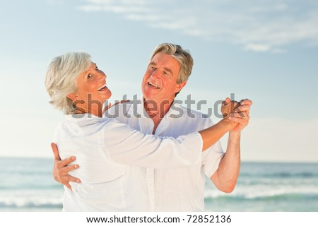 Mature couple dancing on the beach - stock photo