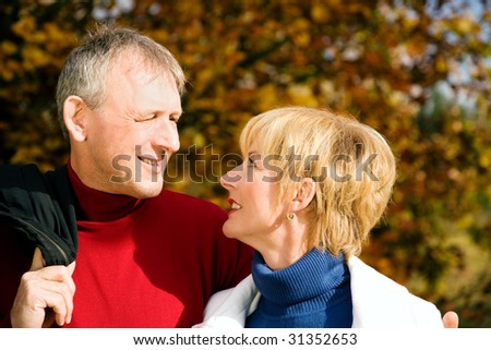 Mature couple deeply in love having a walk holding each other tight