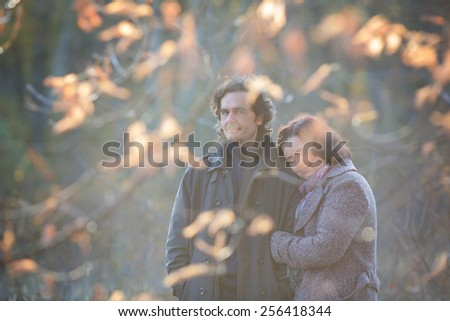 Mature couple deeply in love having a walk holding each other tight in a autumn scenery with yellow leaves. - stock photo