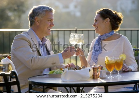 Mature couple dining at outdoor restaurant table, making celebratory toast with wine glasses, smiling, side view - stock photo