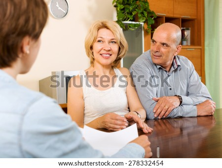 Mature  couple discussing details of private insurance with agent - stock photo