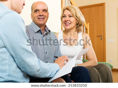 Mature  couple discussing details of private insurance with friendly agent - stock photo