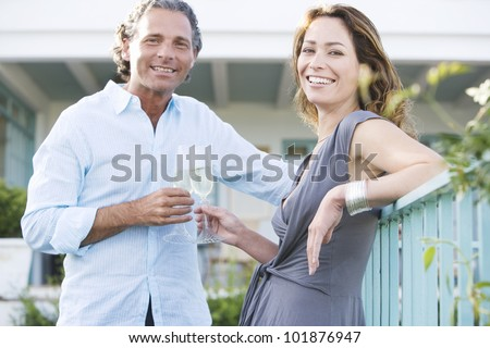 Mature couple drinking champagne while leaning on a hotel's balcony outdoors, smiling at camera.