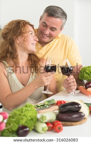 Mature couple drinking red wine in the kitchen and looking at each other. Happy people spending their free time cooking dinner.
