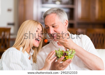 Mature couple eating a salad in the living room